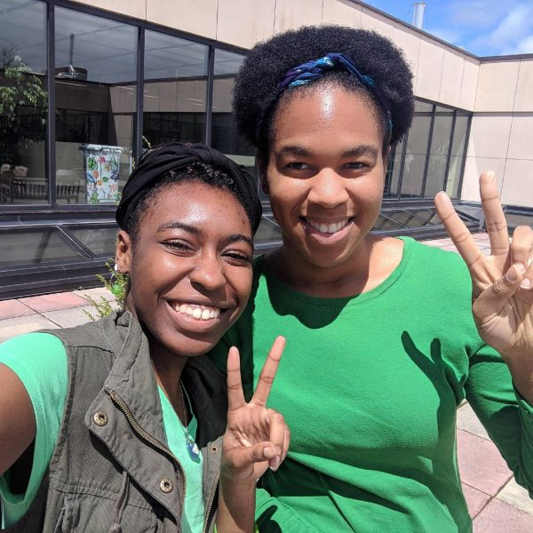 Photo of two students wearing green shirts for