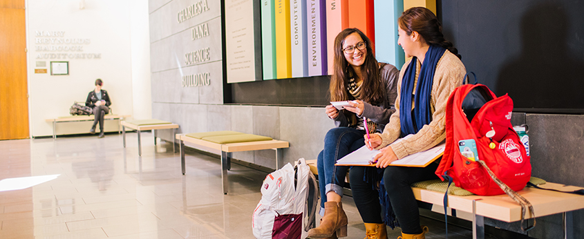 Photo of students sitting in lobby of academic building