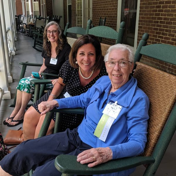 Photo of three alumnae on the porch of Main