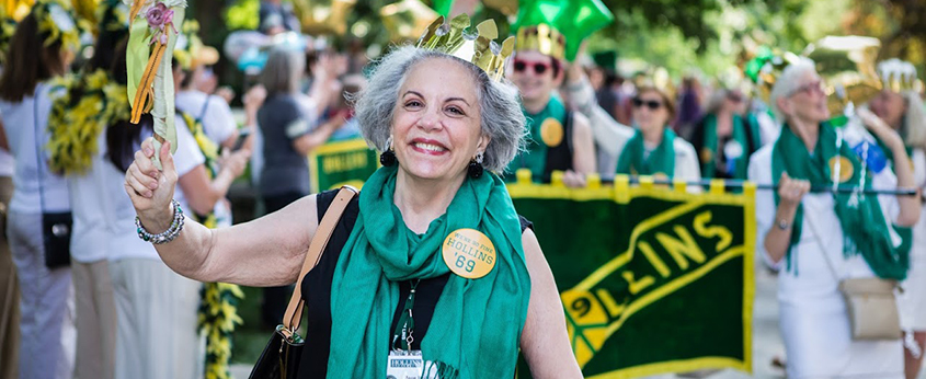 Woman in green scarf and gold crown smiles as she walks reunion parade